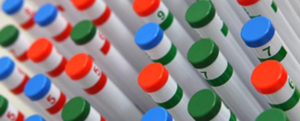 Test tubes with blue, green and red caps.